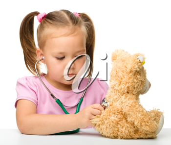 Royalty Free Photo of a Little Girl Checking a Teddy Bear With a Stethoscope