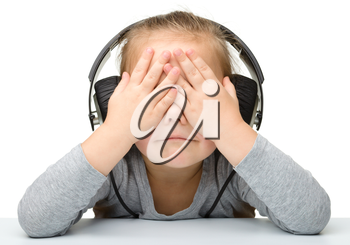 Unhappy girl listening music using headphones while covering her eyes, isolated over white
