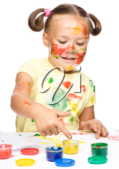 Portrait of a cute cheerful girl playing with paints, isolated over white