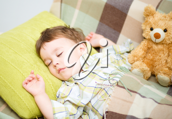 Cute little boy is sleeping with his teddy bear