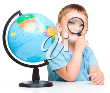 Happy little boy with a globe looking through magnifier, isolated over white