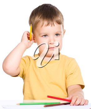 Little boy is holding bunch of color pencils, isolated over white