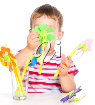 Cute little boy is playing with artificial flowers toys, isolated over white
