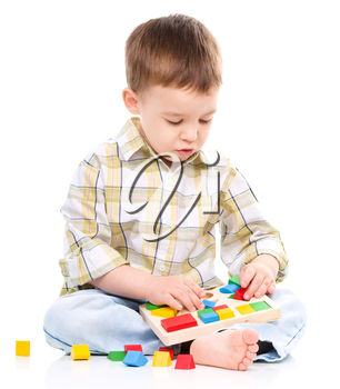 Little boy is playing with toys, isolated over white