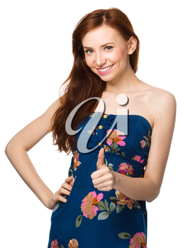 Young woman is showing thumb up gesture, isolated over white
