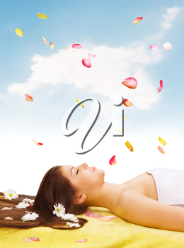Royalty Free Photo of a Woman on a Massage Table With Daisies and Petals