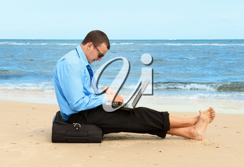 young businessman working with laptop on the beach