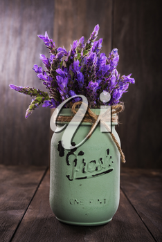 bundle of lavender flowers in retro vase isolated on an old wooden background