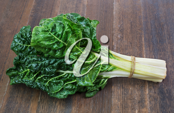 fresh green silverbeet leaves vegetable on  old wooden background
