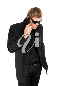 Man wearing black suit and shirt talking on the mobile phone. Isolated