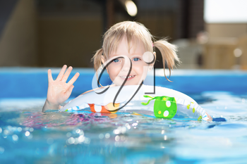 Little blond girl swimming in water pool on inflatable circle