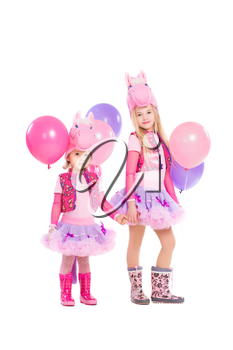 Two little girls posing in pink pony suit. Isolated on white