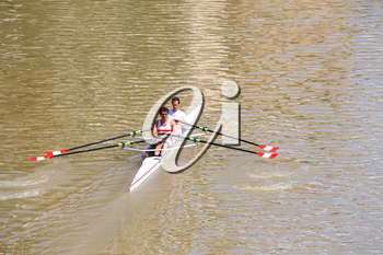 FLORENCE, ITALY - MAY 08, 2014: Two athletes in academic rowing training on the river Arno.
