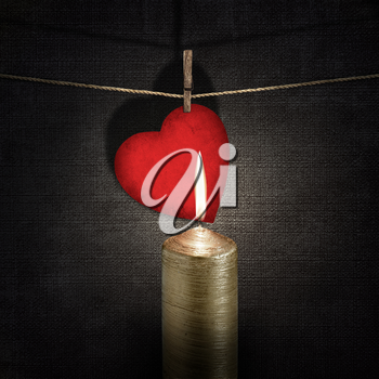 burning candle and red paper heart on a rope over vintage embossed dark backgrounds