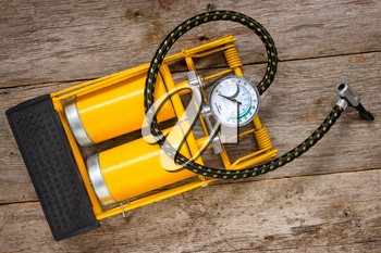 Yellow inflator with gauge on wooden background