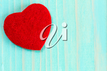 Decorative red heart on blue wooden background