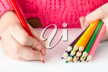 Child draws with colored pencils on paper