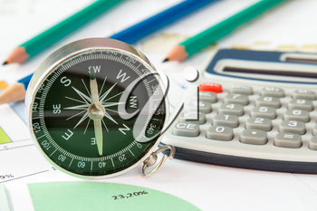 Business graphs and finances with a compass and calculator