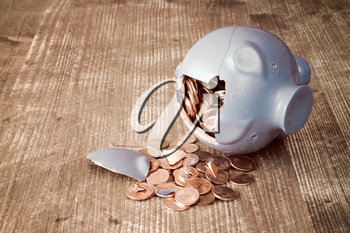 Broken piggy bank with and money on wooden background