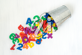 Colorful plastic numbers and letters falling from metal bucket