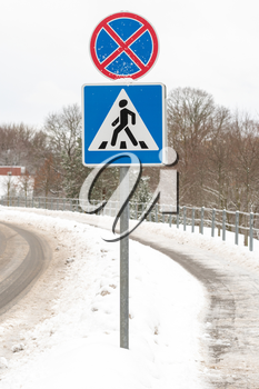 Pedestrian crossing road sign with snow. Drive safely in winter time.