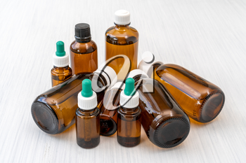 Pile of glass bottles with medicine or essential oil