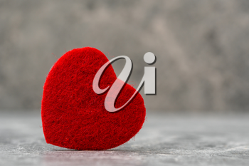 Heart symbol made from red felt on a stone background