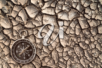 Top view of compass on the cracked dry soil. Ecological disaster concept.