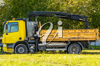 Yellow flatbed truck with crane arm