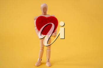 Wooden mannequin holding red heart. Love and passion concept.