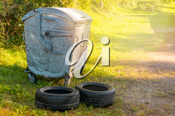 Used car tires left beside the garbage container. Littered with the natural environment.  Illegal garbage disposal. Tires recycling, environmental and ecology problems.