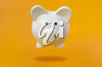 White Piggy bank levitating over a yellow background. Financial concept.