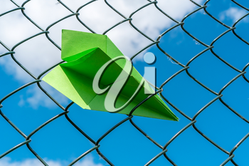 Green paper plane gets stuck in metal fence
