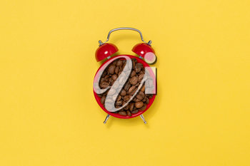 Morning coffee and alarm clock concept. Coffee beans on alarm clock face.