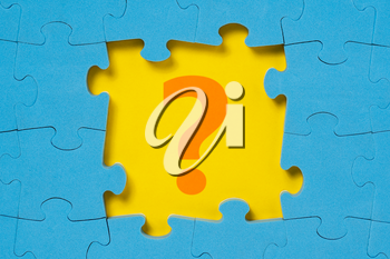 Question mark in a middle of blue puzzle frame. Business concept, help concept