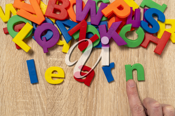 Hand arrange color plastic letters as LEARN word