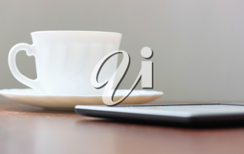 Mobile device and cup of coffee on wood table