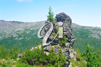 Royalty Free Clipart Image of a Single Rock With Trees Against Mountains