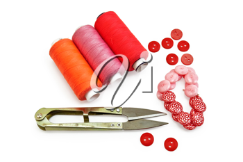 Three spools of thread of orange, red and pink, small metal scissors, red and pink buttons with a pattern isolated on white background