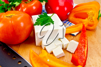 White brine cheese, black knife, parsley, tomatoes, red and yellow peppers, blue napkin on a wooden board