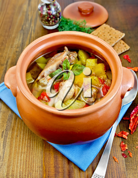 Roast with chicken meat, potatoes and red pepper in a clay pot, blue napkin, spoon, crispbreads, dill and pepper in a jar on a wooden board