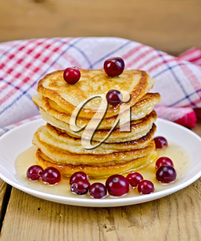A stack of pancakes with cranberries and honey on a white plate on a wooden boards background