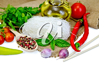 Rice noodles thin, tomatoes, different peppers, chopsticks, garlic, basil, oil, sacking isolated on white background