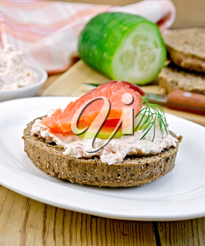 Sandwich of rye bread with cream, cucumber, dill and salmon on a white plate on a wooden board