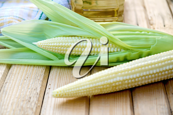 Purified corn cobs, cloth, oil in a bottle on the background of wooden boards