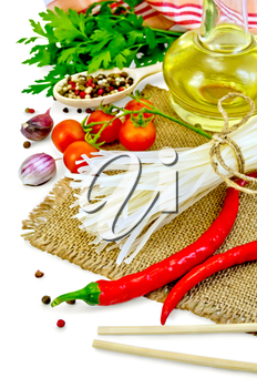 Rice noodles, tomatoes, various peppers, chopsticks, garlic, vegetable oil, burlap, cloth isolated on white background