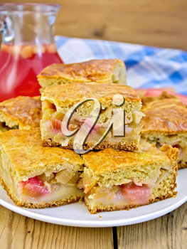 Chunks of sweet cake with rhubarb in a bowl, a jug of juice, napkin on a wooden boards background