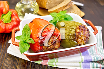 Two sweet peppers stuffed with meat and rice with basil leaves in a brown roasting pan on a napkin on a dark wooden boards background