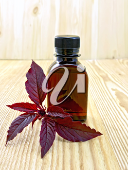 One vial of oil with leaves and flower maroon amaranth on a wooden boards background