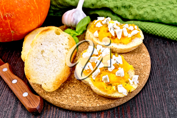 Bruschetta with pumpkin, salted feta cheese, garlic and basil, napkin, knife and orange vegetable on a wooden board background